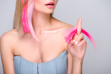 cropped shot of young woman holding cut colorful hair strands and looking at camera isolated on grey Фото со стока - 107912834