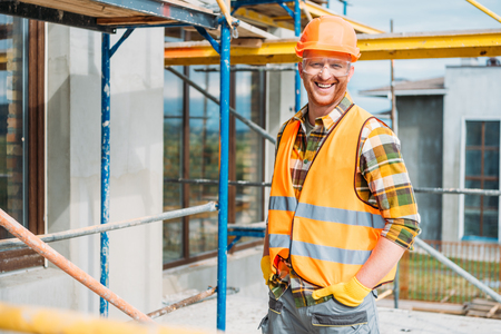 handsome smiling builder in reflective vest and hard hat looking at camera at construction site
