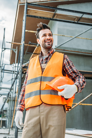 happy builder in reflective vest holding helmet while standing in front of building house and looking away