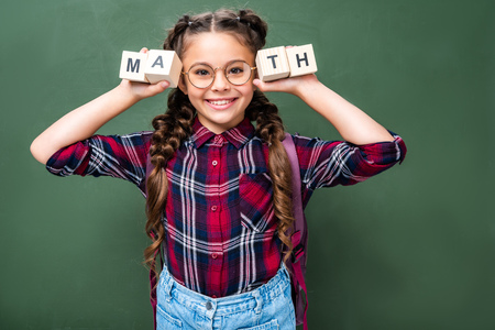 smiling schoolchild holding wooden cubes with word math near blackboard Imagens