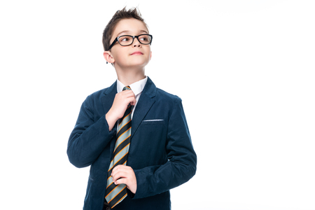 schoolboy in businessman suit tying necktie isolated on white Standard-Bild