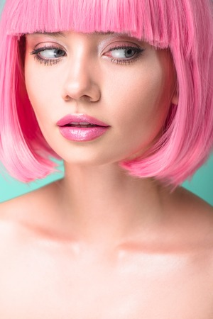 close-up portrait of young woman with pink bob cut looking at side isolated on turquoise Stock Photo