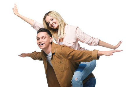 young happy woman piggybacking on boyfriends back and looking at camera isolated on white Stock Photo
