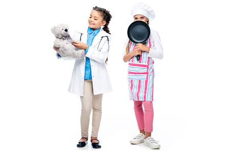 happy schoolchildren in costumes of doctor and chef holding teddy bear and frying pan isolated on white