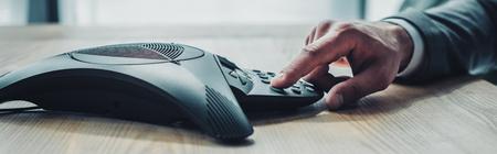 vista laterale ritagliata colpo di imprenditore premendo il pulsante del telefono per conferenze sul posto di lavoro