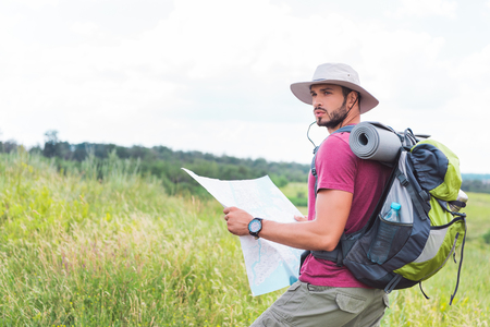 tourist in hat with backpack holding map and standing on green field Banco de Imagens - 107913303