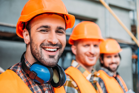 close-up shot of group of equipped builders looking at camera at construction site