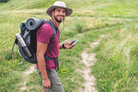 traveler with backpack using smartphone on summer meadow 版權商用圖片