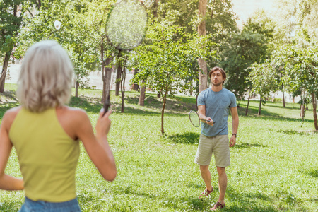 couple playing badminton in green park in summer 写真素材