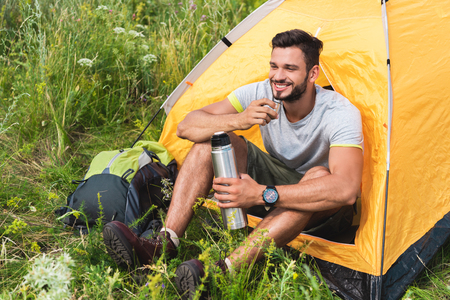 smiling traveler sitting in yellow tent with backpack and drinking coffee from thermos Banco de Imagens
