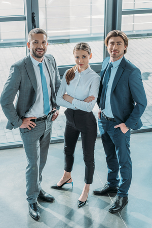 group of successful young business people standing at modern office and looking at camera