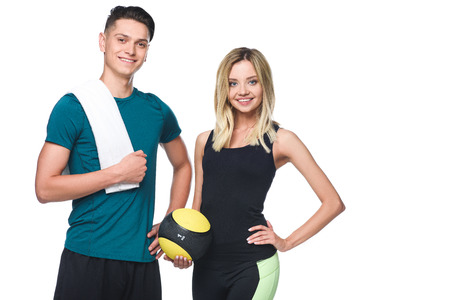 young sporty couple with fitball and towel looking at camera isolated on white