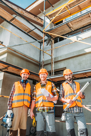 group of smiling equipped builders looking at camera at construction site 版權商用圖片