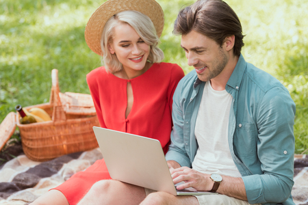 couple using laptop on blanket in park