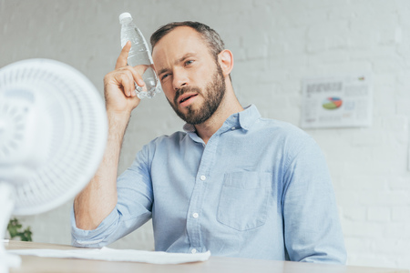 businessman cooling himself with bottle of water and conditioning air with electric fan in office Stock Photo