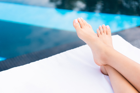 partial view of female feet lying on sunbed at poolside Фото со стока
