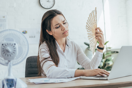 exhausted businesswoman using laptop while conditioning air with electric fan and hand fan in office Stock Photo
