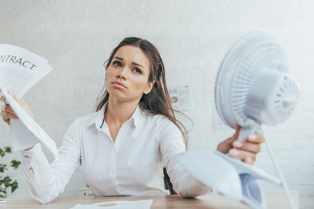businesswoman with paperwork cooling herself with electric fan in office