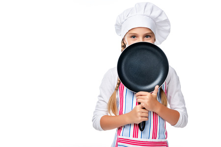 schoolchild in costume of chef looking out from frying pan isolated on white