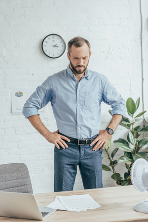sweaty businessman in wet shirt standing in office with laptop, documents and electric fan