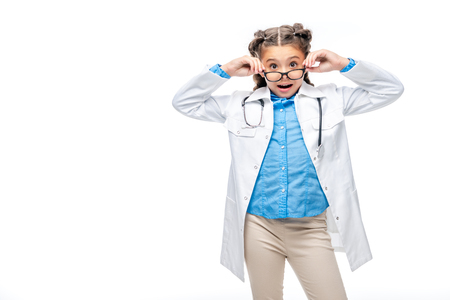 surprised schoolchild in costume of doctor looking above glasses isolated on white