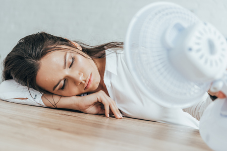 exhausted businesswoman with closed eyes blowing at herself with electric fan in office