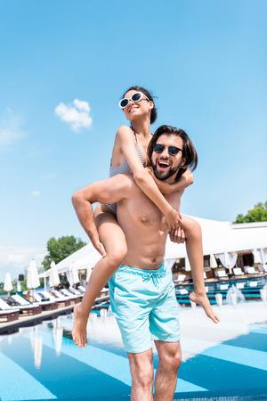 handsome man piggybacking his girlfriend near swimming pool Stok Fotoğraf