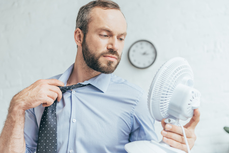 businessman removing tie and blowing on himself with white electric fan