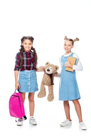 schoolchildren holding teddy bear and looking at camera isolated on white Imagens