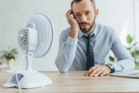 selective focus of businessman in office with white electric fan