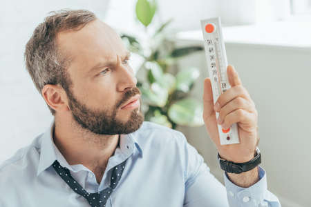 confused businessman in hot office looking at thermometer Archivio Fotografico - 107941971