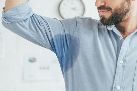 cropped view of sweaty businessman showing blue wet shirt