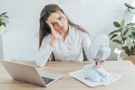 zdenerwowana kobieta siedzi w miejscu pracy z papierkową robotą, laptopem i wentylatorem elektrycznym