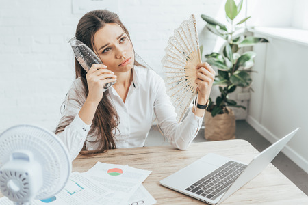 businesswoman cooling herself with electric fan, hand fan and bottle of water at workplace with documents and laptop Stock Photo