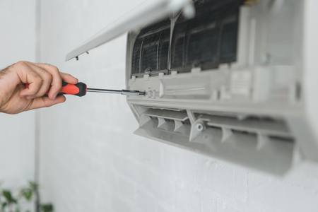 partial view of male worker repairing air conditioner with screwdriver