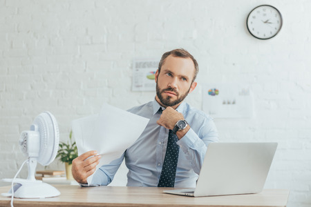 businessman with documents, laptop and electric fan in office Stock Photo