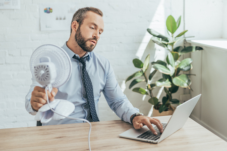 businessman cooling himself with electric fan while using laptop in office