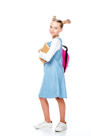 adorable schoolchild with pink backpack holding books and looking at camera isolated on white Imagens