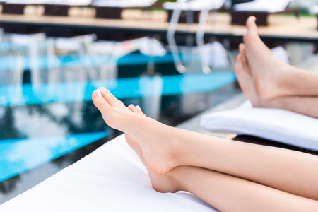 cropped view of couple relaxing on sunbeds near swimming pool 스톡 콘텐츠
