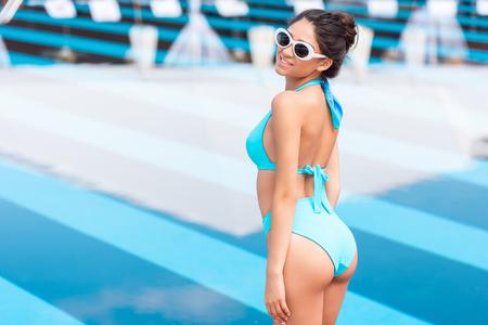 attractive tanned girl posing in blue bikini near swimming pool Фото со стока