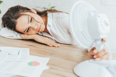exhausted businesswoman blowing at herself with electric fan while lying on table with documents