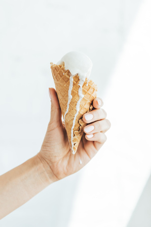cropped view of female hand with melting ice cream in cone