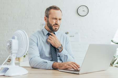bearded businessman working with laptop at workspace with electric fan Stock Photo