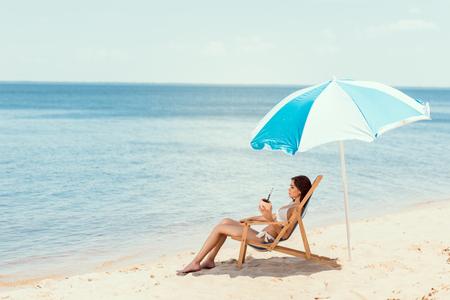 beautiful girl in bikini with coconut cocktail resting on deck chair under beach umbrella near sea