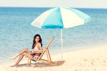 attractive girl in white bikini with book on beach chair under sun umbrella near the sea