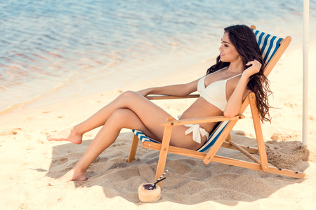 beautiful girl in bikini sitting on beach chair with coconut cocktail on sand
