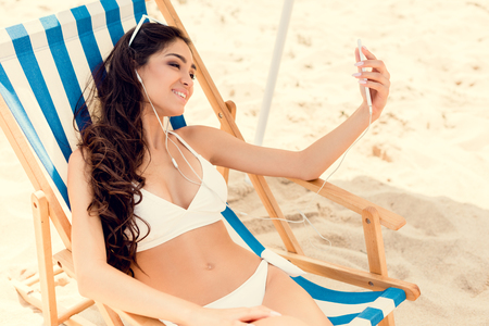 smiling woman taking selfie on smartphone while relaxing on beach chair