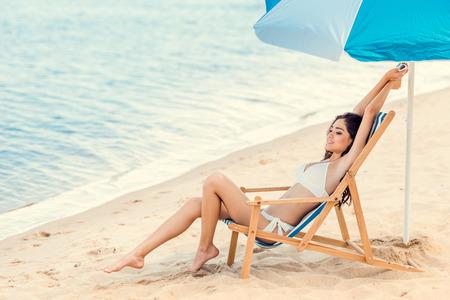 happy girl relaxing on beach chair under sun umbrella near the sea