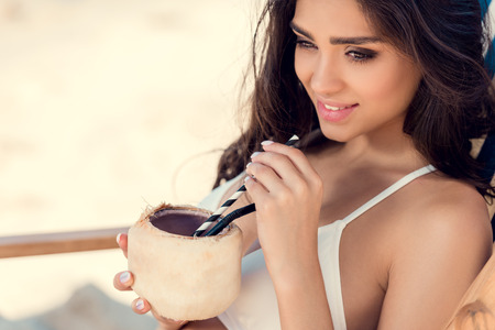 attractive brunette young woman with straws in green coconut drink