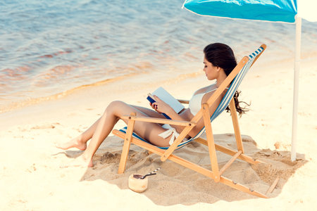 beautiful girl dearing book on beach chair with coconut cocktail on sand